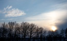 Εντυπωσιακό ηλιοβασίλεμα το χειμώνα με τα σύννεφα και μερικά δέντρα στα ευρωπαϊκά όρη μια κρύα ημέρα το χειμώνα στοκ φωτογραφία