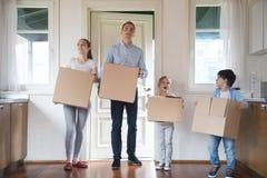Εντυπωσιασμένα οικογενειακά φέρνοντας κιβώτια που κινούνται μέσα προς το καινούργιο σπίτι στοκ φωτογραφίες με δικαίωμα ελεύθερης χρήσης