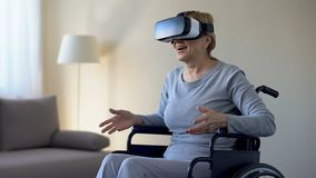 Εντυπωσιασμένη γιαγιά στην αναπηρική καρέκλα που φορά τα προστατευτικά δίοπτρα, παίζοντας το παιχνίδι VR, συσκευή φιλμ μικρού μήκους