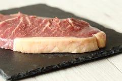 Ενώσεις βόειου κρέατος μπριζόλας κόντρων φιλέτο σε έναν τέμνοντα πίνακα πλακών Στοκ εικόνες με δικαίωμα ελεύθερης χρήσης
