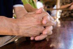 Ενώστε τα χέρια ενός τύπου asain στον ξύλινο πίνακα στοκ εικόνες με δικαίωμα ελεύθερης χρήσης