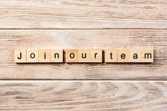 Ενώστε τη λέξη ομάδων μας που γράφεται στον ξύλινο φραγμό ενώστε το κείμενο ομάδων μας στον πίνακα, έννοια στοκ εικόνες