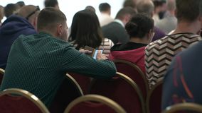 Ενώ στη διάλεξη, ένας νεαρός άνδρας χρησιμοποιεί ένα smartphone Άνθρωποι στο ακροατήριο, οπισθοσκόπο φιλμ μικρού μήκους