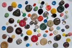 Ενδιαφέρουσα ποικιλία πολλοί φωτεινή ζωηρόχρωμη ποικιλία των στρογγυλών κουμπιών, διαφορετικές συστάσεις, διάμετρος, σε ένα άσπρο Στοκ Εικόνες