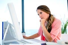 ενδιαφερόμενη επιχειρηματίας που κοιτάζει επίμονα worriedly σε έναν υπολογιστή Στοκ Εικόνες