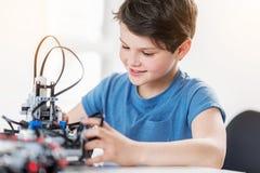 Ενδιαφερόμενο χαμογελώντας αγόρι που ελέγχει το ρομπότ Στοκ Εικόνα