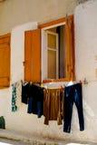 Ενδύματα ημέρας πλυντηρίων που κρεμούν από το ανοικτό παράθυρο Στοκ φωτογραφία με δικαίωμα ελεύθερης χρήσης