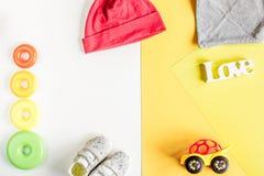Ενδύματα και παιχνίδια μωρών στην άσπρη χλεύη άποψης υποβάθρου τοπ επάνω Στοκ Φωτογραφία