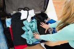 Ενδύματα συσκευασίας γυναικών στη βαλίτσα στοκ εικόνες με δικαίωμα ελεύθερης χρήσης