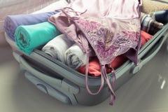 Ενδύματα συσκευασίας στην τσάντα ταξιδιού - αποσκευές και έννοια ανθρώπων Στοκ Εικόνες