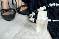 Εξάρτηση γυναικών Μαύρο φόρεμα δαντελλών, σανδάλια παπουτσιών, περιδέραιο και άρωμα στο γκρίζο ξύλινο υπόβαθρο Εξάρτημα βραδιού γ Στοκ Φωτογραφία
