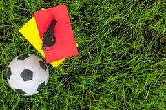 Εξάρτηση διαιτητών ποδοσφαίρου μια κίτρινη και κόκκινη κάρτα με τη σφαίρα στο χορτοτάπητα του σταδίου ποδόσφαιρο τρία σχεδίου εμβ Στοκ εικόνα με δικαίωμα ελεύθερης χρήσης