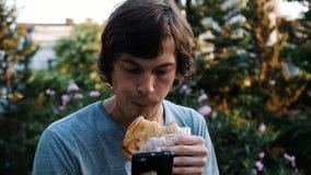 Εξάρτηση στο τηλέφωνο και το διαδίκτυο Ένα άτομο χρησιμοποιεί ένα smartphone και τρώει το khachapuri - πασπαλίστε με ψίχουλα με τ απόθεμα βίντεο