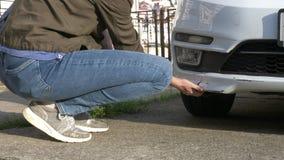 Εξέταση ένα χαλασμένο όχημα Η γυναίκα επιθεωρεί τη ζημία αυτοκινήτων μετά από ένα ατύχημα στοκ φωτογραφία με δικαίωμα ελεύθερης χρήσης
