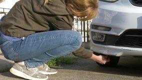 Εξέταση ένα χαλασμένο όχημα Η γυναίκα επιθεωρεί τη ζημία αυτοκινήτων μετά από ένα ατύχημα στοκ εικόνα με δικαίωμα ελεύθερης χρήσης