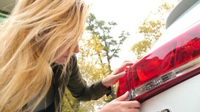 Εξέταση ένα χαλασμένο όχημα Η γυναίκα ξανθή επιθεωρεί τη ζημία αυτοκινήτων μετά από ένα ατύχημα 4k, σε αργή κίνηση απόθεμα βίντεο