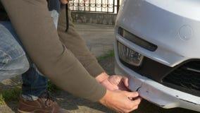 Εξέταση ένα χαλασμένο όχημα Το άτομο επιθεωρεί τη ζημία αυτοκινήτων μετά από ένα ατύχημα στοκ εικόνες