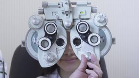 Εξέταση ματιών γυναικών πορτρέτου optometrist στον οφθαλμολόγο που χρησιμοποιεί phoropter στενό επάνω Χαριτωμένο κοίταγμα χαμόγελ απόθεμα βίντεο