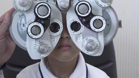 Εξέταση ματιών μικρού παιδιού optometrist στον οφθαλμολόγο που χρησιμοποιεί phoropter στενό επάνω Χέρι του μεταβαλλόμενου γυαλιού φιλμ μικρού μήκους