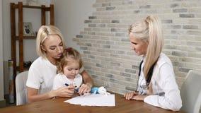 Εξέταση παιδικών υγειών Νέες μητέρα και αυτή λίγος όμορφος παιδίατρος επίσκεψης κορών Φιλική κλινική παιδικών υγειών απόθεμα βίντεο