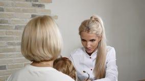 Εξέταση παιδικών υγειών Νέες μητέρα και αυτή λίγος όμορφος οικογενειακός γιατρός επίσκεψης κορών Φιλικός ΩΤΟΡΙΝΟΛΑΡΥΓΓΟΛΟΓΙΚΟΣ πα φιλμ μικρού μήκους
