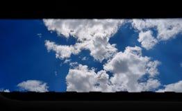 Εξέταση τα σύννεφα μέσω του παραθύρου στοκ φωτογραφία