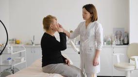 Εξέταση του προσώπου και του δέρματος ενήλικη γυναίκα στο beautician γραφείων απόθεμα βίντεο