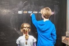 Εξήγηση και κορίτσι αγοριών κάτι στον πίνακα κιμωλίας Στοκ Εικόνες