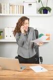 Εξαγριωμένη επιχειρηματίας που κραυγάζει σε κινητό με το έγγραφο διαθέσιμο Στοκ Φωτογραφίες