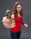 Εξαγριωμένη νέα γυναίκα με το πυροβόλο όπλο που εκφράζει την εκδίκηση, το μίσος ή την κατηγορία Στοκ φωτογραφία με δικαίωμα ελεύθερης χρήσης