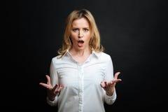 Εξαγριωμένη ώριμη γυναίκα που φωνάζει στο μαύρο χρωματισμένο στούντιο Στοκ Εικόνες