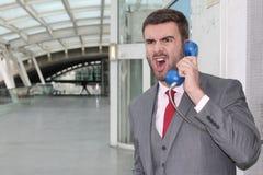 Εξαγριωμένος επιχειρηματίας που κραυγάζει στο δημόσιο τηλέφωνο Στοκ εικόνες με δικαίωμα ελεύθερης χρήσης