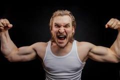 Εξαγριωμένος μαχητής που παρουσιάζει τέλειους δικέφαλους μυς του Στοκ φωτογραφία με δικαίωμα ελεύθερης χρήσης