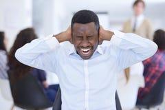 Εξαγριωμένος μαύρος επιχειρηματίας που κουράζεται της εργασίας στο πρόγραμμα στο γραφείο Στοκ Εικόνες