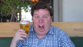 Εξαγριωμένος νεαρός άνδρας που κρατά ένα ποτήρι της μπύρας και που κραυγάζει στον πανικό απόθεμα βίντεο
