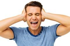 Εξαγριωμένος νεαρός άνδρας που καλύπτει τα αυτιά με τα χέρια Στοκ Φωτογραφίες