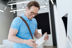 Εξαιρετικά ευτυχές άτομο που εξετάζει το πιάτο πληροφοριών προϊόντων στην αίθουσα εκθέσεως Στοκ εικόνες με δικαίωμα ελεύθερης χρήσης