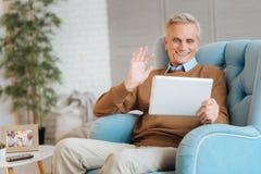 Εξαιρετικά ευτυχές ηλικιωμένο άτομο που κυματίζει κατά τη διάρκεια της τηλεοπτικής κλήσης Στοκ Εικόνες