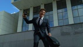 Εξαιρετικά ευτυχής επιχειρηματίας που χορεύει υπαίθρια κοντά στο κτίριο γραφείων, επιτυχία απόθεμα βίντεο