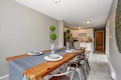 Εξαιρετικό dinning δωμάτιο με τους γκρίζους τοίχους και το μακρύ πίνακα Στοκ φωτογραφία με δικαίωμα ελεύθερης χρήσης