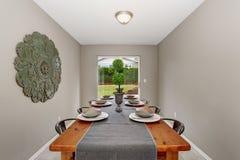 Εξαιρετικό dinning δωμάτιο με τους γκρίζους τοίχους και το μακρύ πίνακα Στοκ Φωτογραφία