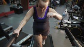 Εξαντλημένη υπέρβαρη γυναίκα που περπατά treadmill, που υφίσταται τα προβλήματα υγείας απόθεμα βίντεο