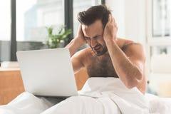 Εξαντλημένος άνδρας εργαζόμενος που χρησιμοποιεί το lap-top στο σπίτι Στοκ εικόνες με δικαίωμα ελεύθερης χρήσης
