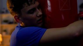 Εξαντλημένος έφηβος που αγκαλιάζει punching την τσάντα μετά από το εντατικό workout, ικανότητα, αθλητισμός στοκ φωτογραφία με δικαίωμα ελεύθερης χρήσης