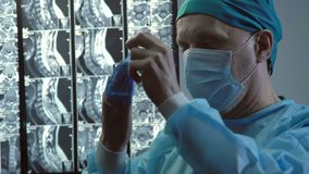 Εξαντλημένος αρσενικός χειρούργος που βγάζει τα ιατρικές γάντια και τη μάσκα προσώπου, μακροχρόνια λειτουργία φιλμ μικρού μήκους