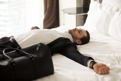 Εξαντλημένος επιχειρηματίας που βάζει στο κρεβάτι στο δωμάτιο ξενοδοχείου Στοκ εικόνα με δικαίωμα ελεύθερης χρήσης