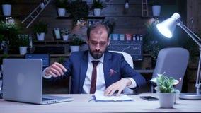 Εξαντλημένος επιχειρηματίας που εργάζεται αργά τη νύχτα στο γραφείο απόθεμα βίντεο