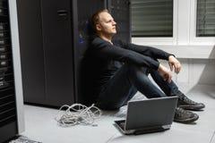 Εξαντλημένος μέσος ενήλικος αρσενικός τεχνικός ενάντια στο ράφι κεντρικών υπολογιστών σε Datacenter στοκ εικόνα με δικαίωμα ελεύθερης χρήσης
