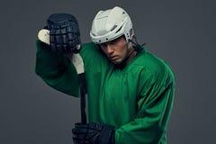 Εξαντλημένος παίκτης χόκεϋ που φορά το πράσινο προστατευτικό εργαλείο και το άσπρο κράνος που στέκονται με το ραβδί χόκεϋ Απομονω Στοκ Φωτογραφίες