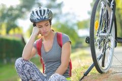 Εξαντλημένο κορίτσι που βάζει στο έδαφος μετά από τη φυλή ποδηλάτων Στοκ Φωτογραφίες